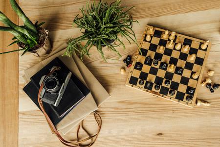 チェスの駒、鉢植えな植物の本の上にヴィンテージカメラとチェス盤