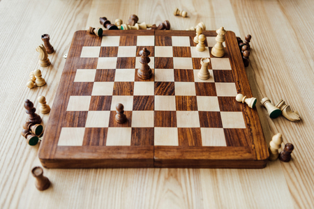 chess figures scattered on chessboard at the table