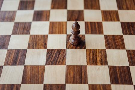 木製のチェス盤に黒のチェスの駒