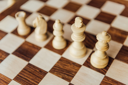 white chess pieces standing in row on chessboard