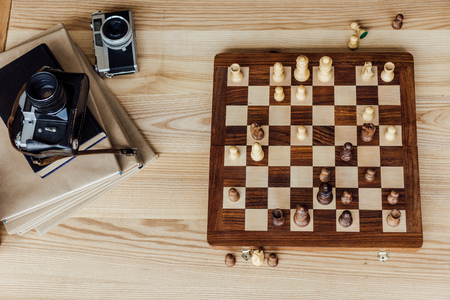 Above view of chess board set with old vintage cameras and books