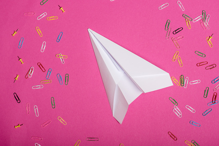 white paper plane and colorful paper clips isolated on pink