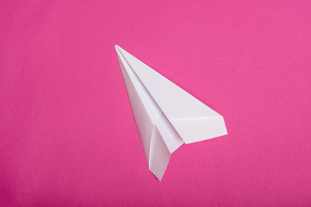 white paper plane isolated on pink