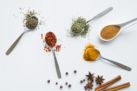 Verschillende gedroogde aromatische kruiden in metaal en keramische lepels Stockfoto