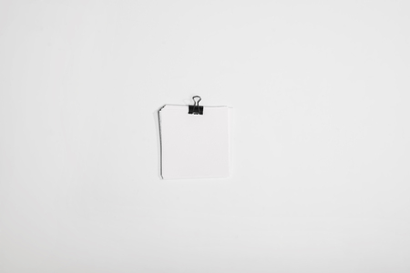 top view of little stack of white note papers with binder clip