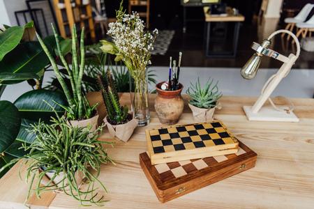 チェス ボードとテーブルの上のレトロなランプが付いている鍋の緑の植物