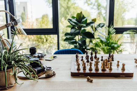 chess board, old vintage cameras on workplace with green plants around