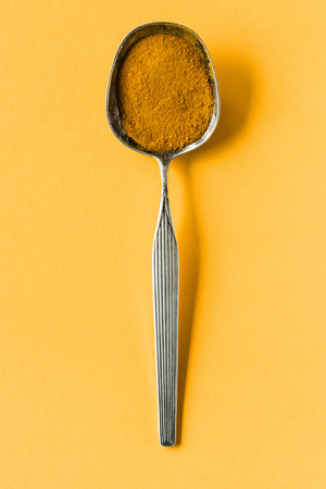 metal spoon with curry powder on yellow surface Stock Photo