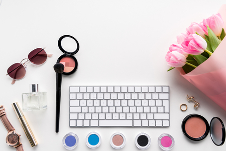 flat lay with computer keyboard, different cosmetics, accessories and flowers Stok Fotoğraf