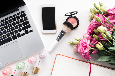 Top view of laptop, smartphone with blank screen, bouquet of flowers and cosmetics