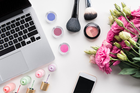 flat lay with various cosmetics, bouquet of flowers, laptop and smartphone