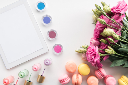 Flat lay of digital tablet with blank screen, tasty cookies, bouquets of flowers and cosmetics