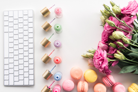 flat lay with keyboard, colorful nail polishes, macarons and flowers Stock Photo