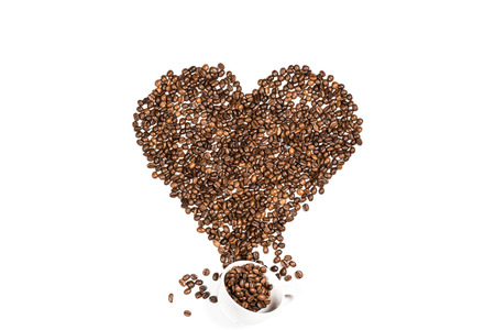 White cup and heart symbol made from coffee seeds