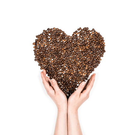 Human hands making heart symbol made from coffee seeds