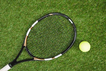 テニス ラケットとボールの緑の芝生の上に横たわる 写真素材