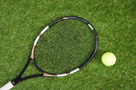 tennis racket and ball lying on green lawn Фото со стока
