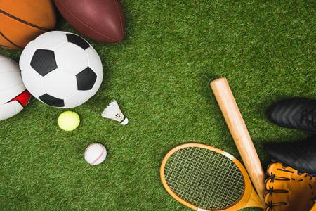 various sport balls, baseball bat and glove, badminton racket on green lawn