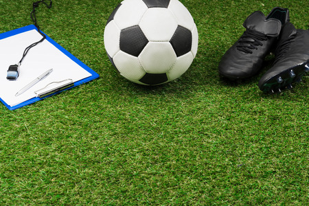 clipboard with soccer ball and boots on grass pitch