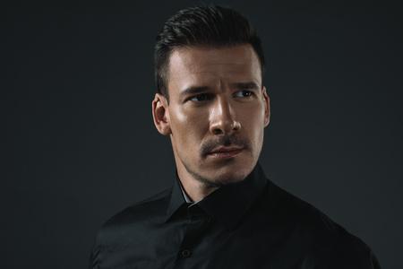 黒の服がよそ見で深刻なスタイリッシュな男の肖像