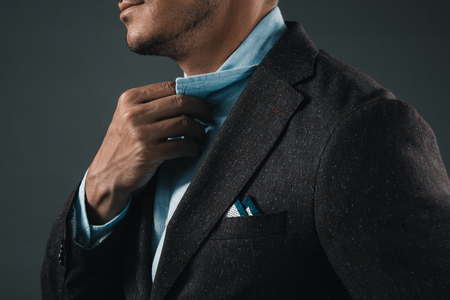 cropped out: partial view of man holding shirt collar Stock Photo