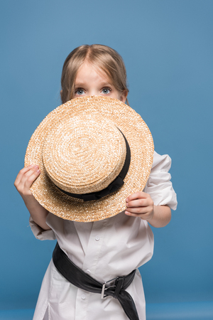scared adorable little girl with straw boater