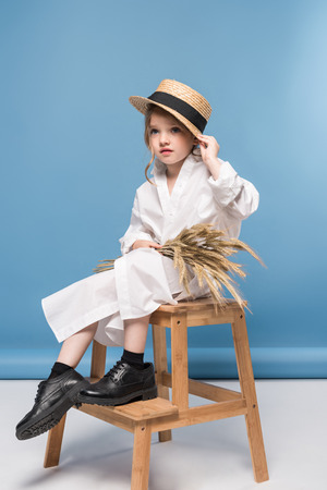白いドレスと小麦の耳を持ってストロー カンカン帽を座っている美しい少女 写真素材