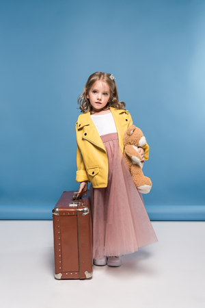 pensive little girl holding teddy bear and suitcase in studio