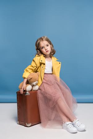 テディベアを押しながらスタジオでスーツケースの上に座ってのピンクのスカートの女の子 写真素材