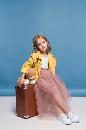 little girl in pink skirt holding teddy bear and sitting on suitcase in studio