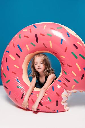 도넛 모양의 튜브 수영에 앉아있는 어린 소녀