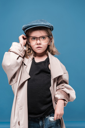 caucasian child girl in glasses and oversized coat looking away