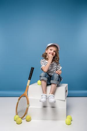 어린 소녀 테니스 raquet와 공을 웃는