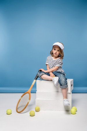 little girl sitting on white boxes and holding tennis raquet