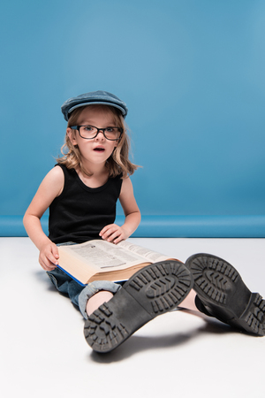 kid girl reading book with facial expression while sitting on the floor
