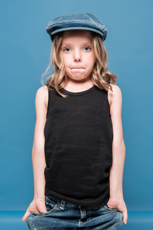 stylish little girl looking at camera with hands in pockets