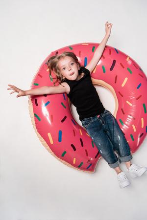 girl resting on swimming tube in shape of doughnut
