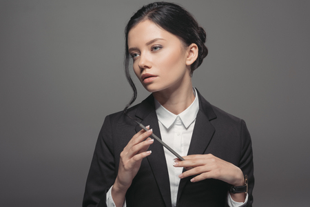 thoughtful caucasian businesswoman holding pencil and looking away