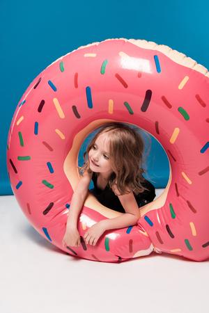 도넛 형의 튜브와 함께 노는 어린 소녀 스톡 콘텐츠