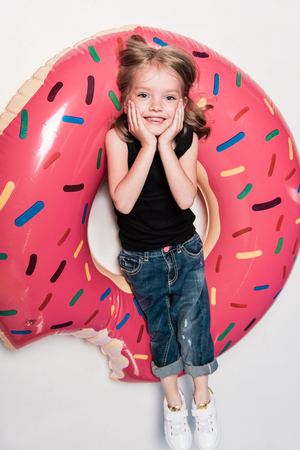 girl smiling while lying on swimming tube in form of doughnut