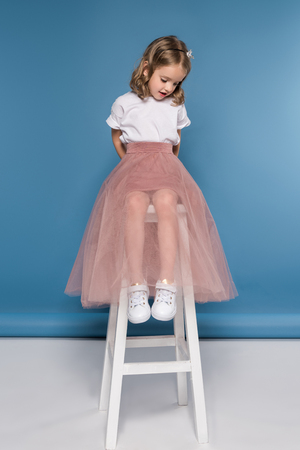 Niña en falda rosa sentado en la escalera y mirando hacia abajo Foto de archivo - 82697298