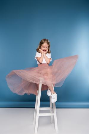 사다리에 앉아서 내려다 보면서 핑크색 치마에 어린 소녀