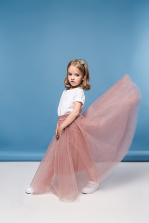 little girl in pink skirt posing in studio and looking at camera Stock Photo
