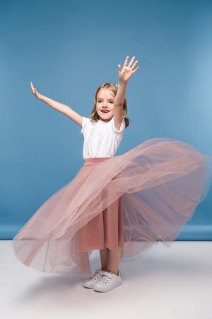 little girl in pink skirt posing in studio