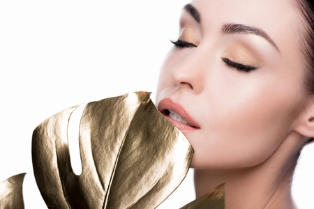close up view of sensual woman holding big golden leaf near lips