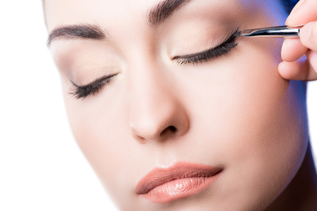 Makeup artist applying eyeliner arrows on face. hand of woman using makeup brush