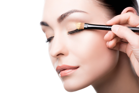 Makeup artist using brush to apply eye shadow on face of woman Archivio Fotografico