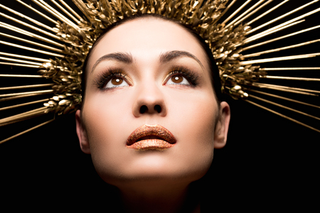 close up view of attractive woman in golden headpiece looking up Stock Photo