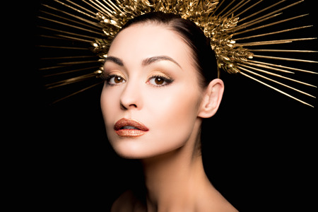 portrait of gorgeous woman in golden headpiece looking at camera