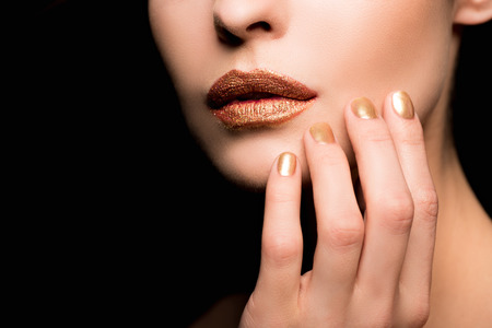 cropped view of woman with makeup and golden manicure Stock Photo